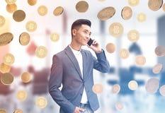Asiatisk affärsman på telefonen, bitcoinregn royaltyfri fotografi
