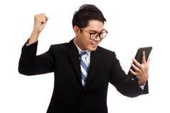 Asiatisk affärsman som är lycklig med framgång med minnestavlaPC fotografering för bildbyråer