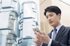 Asiatisk affärsman som använder mobiltelefonen arkivfoton