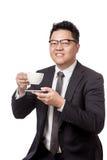 Asiatisk affärsman som dricker kaffe och leende Arkivbild