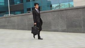 Asiatisk affärsman som går ner gatan lager videofilmer