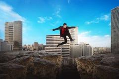 Asiatisk affärsman som hoppar över den brutna vägen Arkivbild