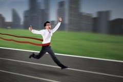 Asiatisk affärsman som korsar mållinjen Arkivfoto