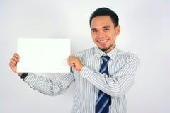 Asiatisk affärsman som ler hållen det tomma papperet som isoleras på vit Fotografering för Bildbyråer
