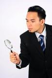 Asiatisk affärsman som ser till och med ett förstoringsglas som isoleras på vit Arkivfoton