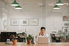 Asiatisk affärsman som talar på en mobiltelefon på hans kontorsskrivbord royaltyfri fotografi