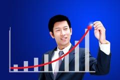 Asiatisk affärsman som tecknar en graf Arkivbild