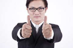 asiatisk affärsman som visar upp tum Arkivbild