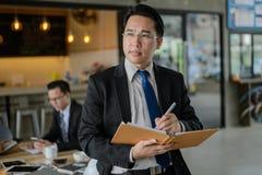 Asiatisk aff?rsman som rymmer en bok och en penna f?r att skriva ett aff?rsplan Honom anseende och se framåtriktat och att tänka  royaltyfria foton