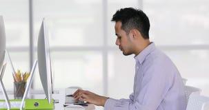 Asiatisk aff?rsman som skriver p? datortangentbordet lager videofilmer
