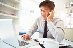 Asiatisk affärsman Working From Home som använder mobiltelefonen Fotografering för Bildbyråer