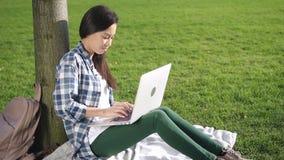 Asiatisk amerikansk kvinna som använder bärbar datordatoren som sitter längs högskolauniversitetsområde stock video