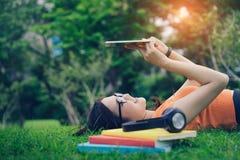 Asiatisk användande minnestavla för ung flicka med headphonen royaltyfria bilder