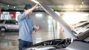 Asiatisk auto mekaniker som kontrollerar bilen genom att anv?nda minnestavlan arkivbilder