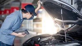 Asiatisk auto mekaniker som kontrollerar bilen genom att anv?nda minnestavlan arkivfoto