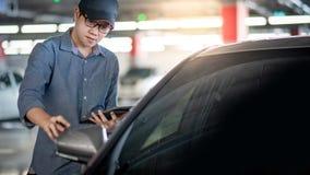 Asiatisk auto mekaniker som kontrollerar bilvingspegeln arkivfoto