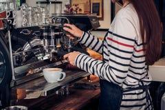 Asiatisk baristakvinna som gör kaffecappuccino på kafét med maskinen på räknarestången i eatery-, mat- och drinkservicebegrepp royaltyfri bild