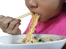 Asiatisk barnflicka för nära övre mun som äter nudlar arkivfoto