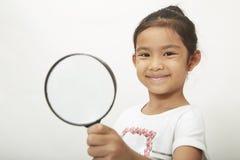 asiatisk barnflicka med ett förstoringsglas arkivbilder