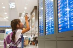 Asiatisk barnflicka med ryggs?cken som kontrollerar hennes flyg p? informationsbr?det i terminal f?r internationell flygplats royaltyfri foto