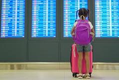 Asiatisk barnflicka med ryggs?cken som kontrollerar hennes flyg p? informationsbr?det i terminal f?r internationell flygplats royaltyfri bild