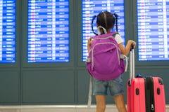 Asiatisk barnflicka med ryggs?cken som kontrollerar hennes flyg p? informationsbr?det i terminal f?r internationell flygplats royaltyfria foton