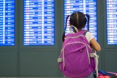 Asiatisk barnflicka med ryggs?cken som kontrollerar hennes flyg p? informationsbr?det i terminal f?r internationell flygplats royaltyfria bilder
