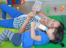 Asiatisk barnflicka och moder som ligger på madrassen och spelar bildkortet för högra Brain Development på lekrummet arkivbild
