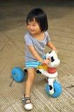 Asiatisk barnflicka som leker på toyen med hjul Arkivbilder