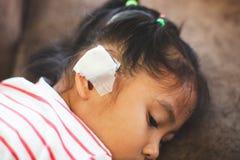Asiatisk barnflicka som såras på örat Barnets öra med förbinder, efter hon har varit olyckan royaltyfria bilder