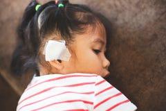 Asiatisk barnflicka som såras på örat Barnets öra med förbinder, efter hon har varit olyckan arkivbild