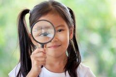 Asiatisk barnflicka som ser till och med ett förstoringsglas arkivbild
