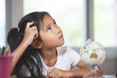 Asiatisk barnflicka som tänker, när göra läxa i hennes rum royaltyfri fotografi