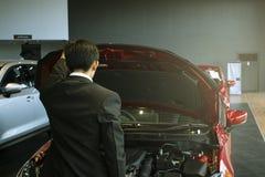 Asiatisk bil för öppen dörr för man med teknologimotorn på oskarp bakgrund Serva eller transportera automatiskt för automatiskt e royaltyfri fotografi