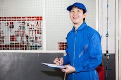 Asiatisk biltekniker som ler i garageservice Royaltyfri Foto