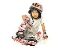 Asiatisk borrad liten flickakänsel, medan fall ner i rullskridskor Arkivbilder