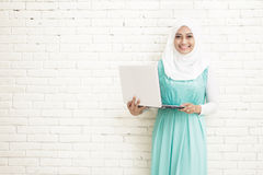 asiatisk bärande hijab för ung kvinna som rymmer en bärbar dator Arkivbilder