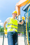 Asiatisk byggmästare med grävskopan på konstruktionsplats Royaltyfria Bilder
