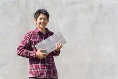 Asiatisk byggmästareman som rymmer konkreta kvarter Arkivfoton