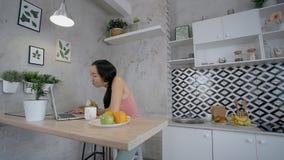 Asiatisk dam som äter äpplet och kommunikation på hennes bärbar dator i köket stock video