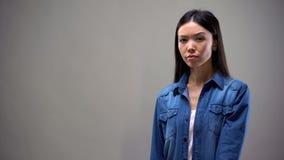 Asiatisk dam som ser suspiciously kameran som isoleras på grå bakgrund, misstro royaltyfri foto
