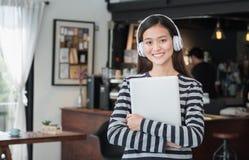 Asiatisk dator för bärbar dator för tonåringflickakram och lyssnande musik med Royaltyfri Foto