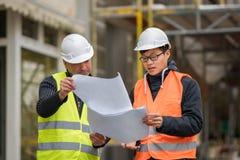 Asiatisk deltagare i utbildningtekniker på arbete på konstruktionsplats med den höga chefen Arkivbilder