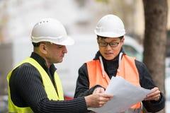 Asiatisk deltagare i utbildningtekniker på arbete på konstruktionsplats med den höga chefen Arkivfoto