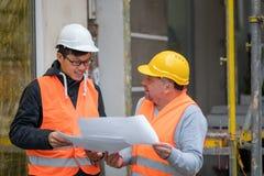 Asiatisk deltagare i utbildningtekniker på arbete på konstruktionsplats med den höga chefen Royaltyfria Foton