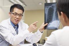 Asiatisk doktor och patient royaltyfria foton