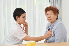 Asiatisk doktor som kontrollerar upp hennes tålmodiga pensionär arkivbilder
