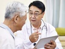 Asiatisk doktor som talar till patienten Arkivfoto