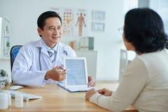 Asiatisk doktor som talar till patienten arkivbild