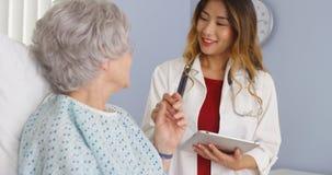 Asiatisk doktorsinnehavhand av den äldre kvinnapatienten i sjukhus royaltyfria foton